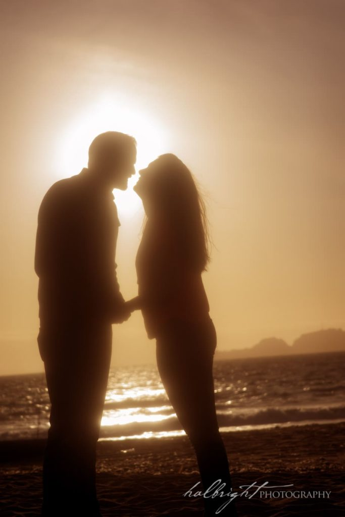 couple photographed together in Silhouette for their engagement portrait session - Baker Beach - San Francisco, California