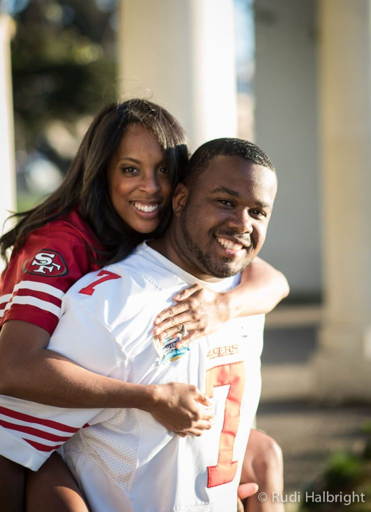Couple wearing football jerseys Engagement Portrait near Lake Merritt in Oakland, California | Oakland Portrait Photographer