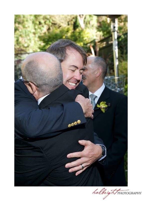 Guest hugging groom at GLBT Wedding in San Francisco