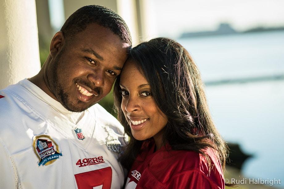 Couple wearing football jerseys Engagement Portrait near Lake Merritt in Oakland, California   Oakland Portrait Photographer