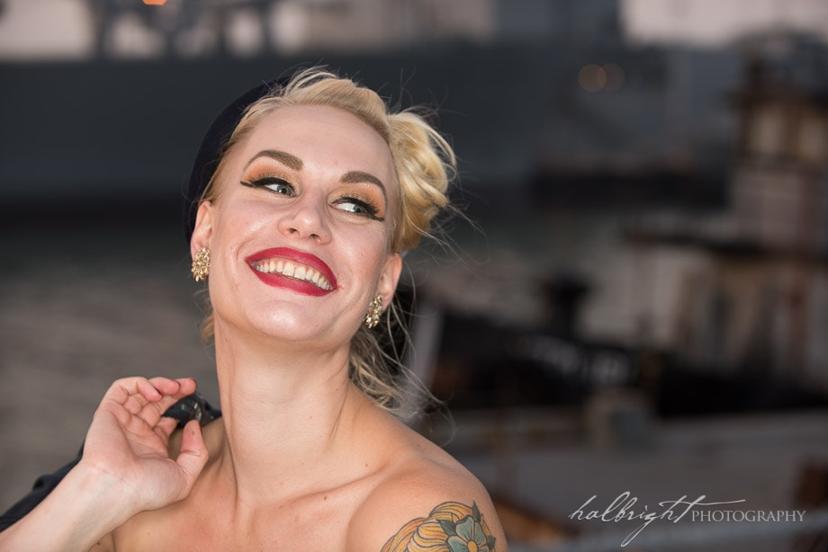 Model poses in front of old tug boat in vintage outfit near U.S.S. Hornet in Alameda, CA