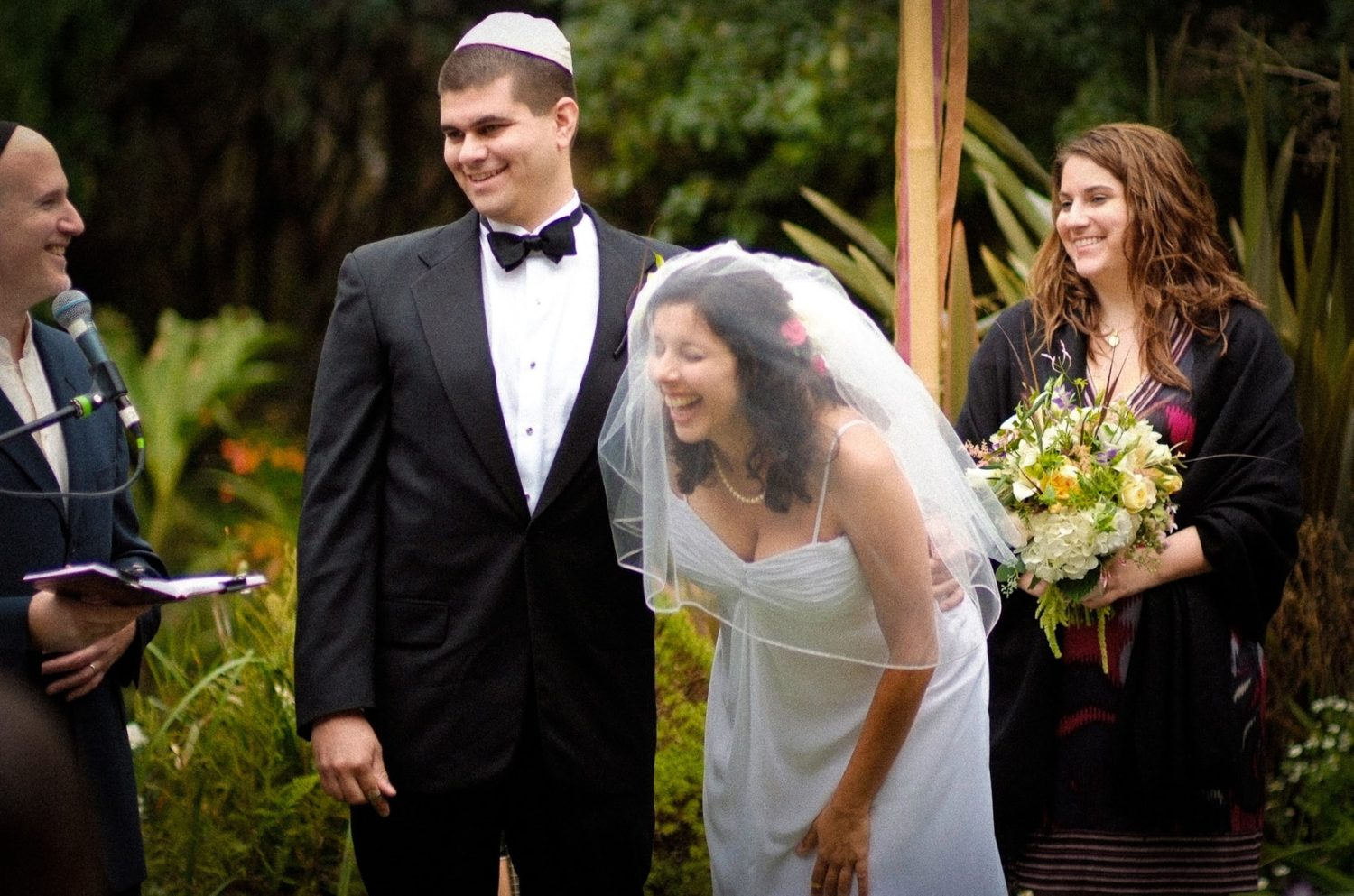 A groom wearing a suit and tie standing next to his bride wearing her wedding dress and veil under the chuppah at their Jewish Wedding
