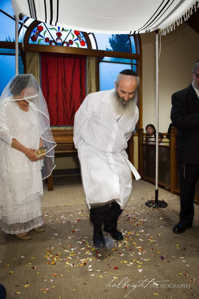 The groom stomps on the glass at his Berkeley, Jewish, Wedding at Congregation Beth Israel to symbolize the impermenance and brokenness of all things.
