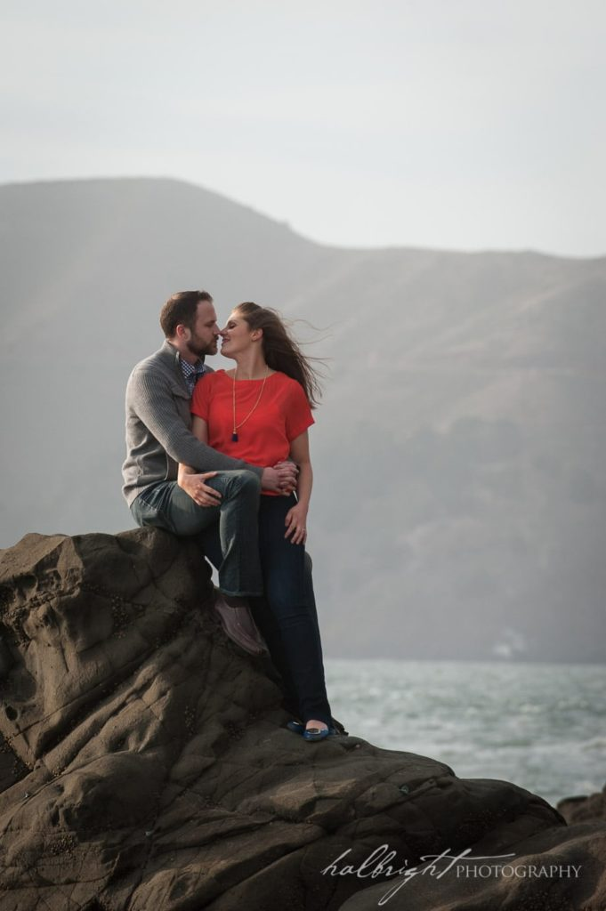 Couple takes a moment to connect as they sit on a rock overlooking the Pacific Ocean at Baker Beach San Francisco | Engagement Portrait - San Francisco