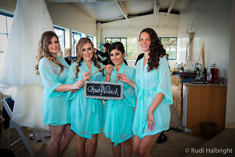 Bridesmaids dressed in cyan colored robes holding sign with names of bride and groom - mavericks half moon bay - wedding