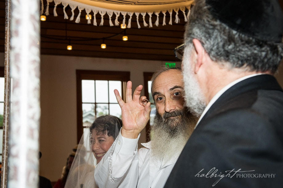 The groom holds up the wedding ring before putting it on his bride at their Modern Orthodox Jewish Wedding at Congregation Beth Israel in Berkeley, California