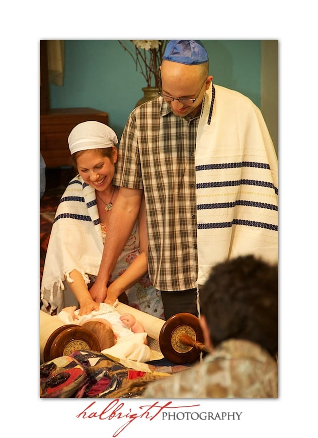 Parents bless their child on the torah at Jewish baby naming ceremony