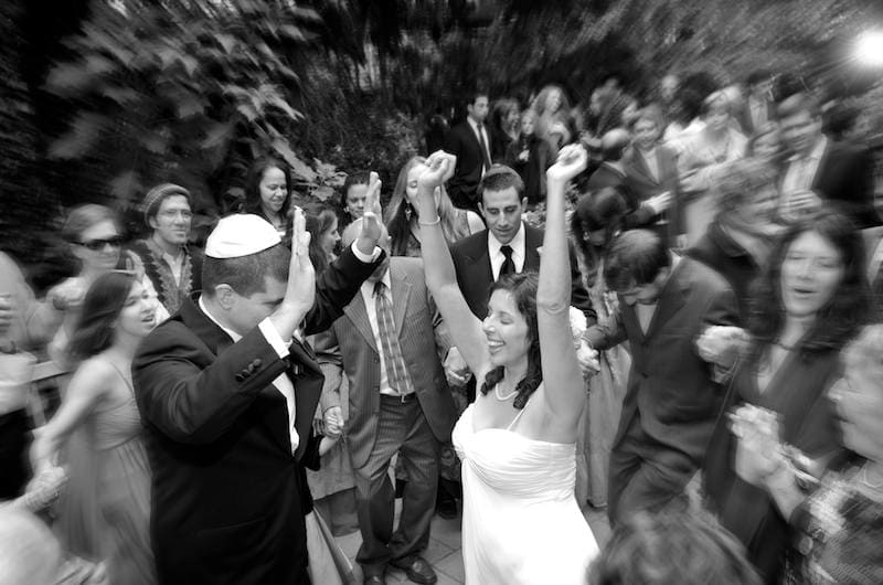 Bride raises her arms in excitement during her first dance with her groom - Wedding reception