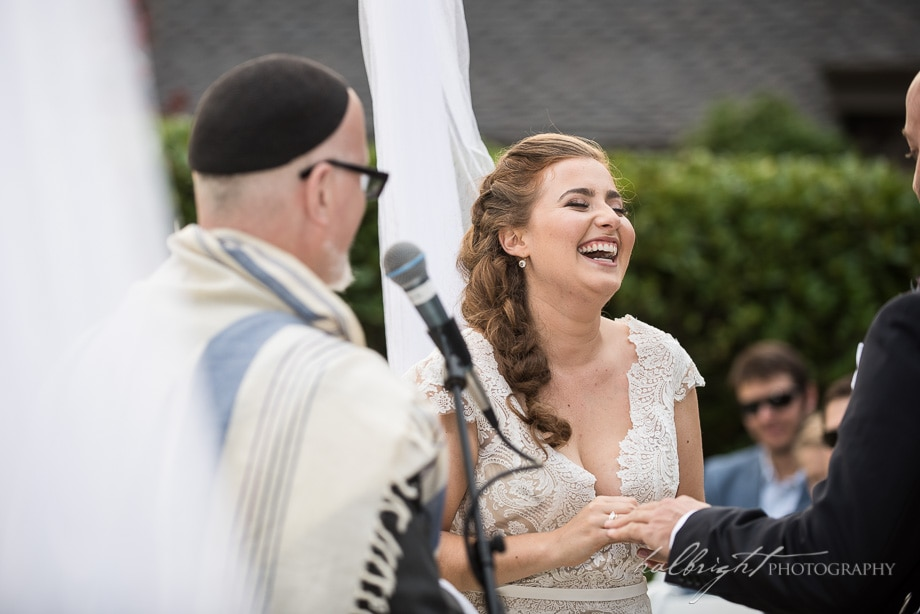 bride laughs with joy as groom puts her ring on her hand - brazil room wedding - tilden park - berkeley wedding