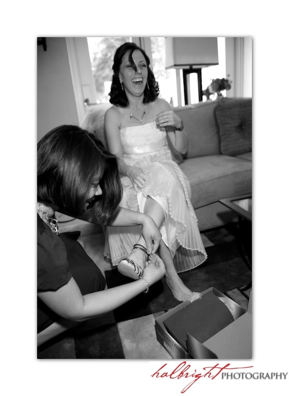 Jill Chatanow is getting helping putting on her weddings shoes from her friend.