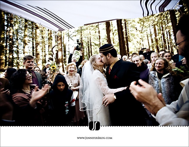 Bride and Groom kiss under the chuppah surrounded by friends in a Redwood Grove - Oakland Wedding