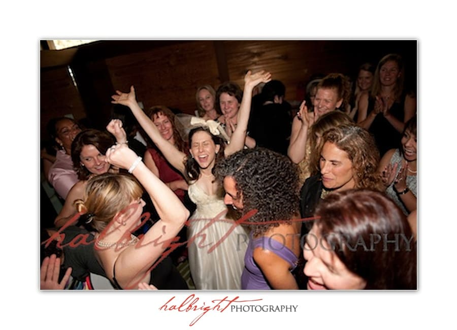 Bride raises her arms in excitement in gathering before wedding - mills college wedding