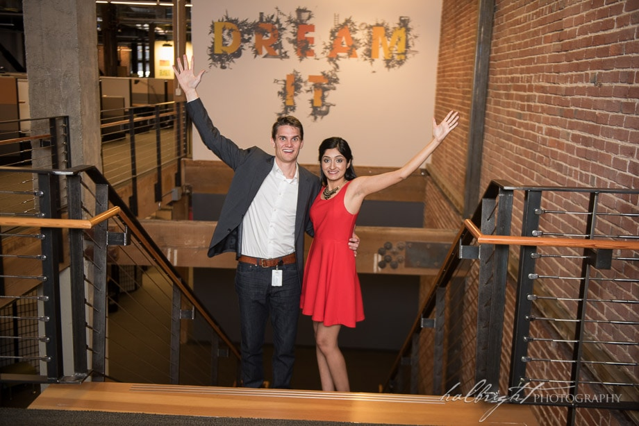 "Pooja and Grant stand in front of a sign saying ""Dream It"" at the Adobe Office during their San Francisco engagement portrait session"