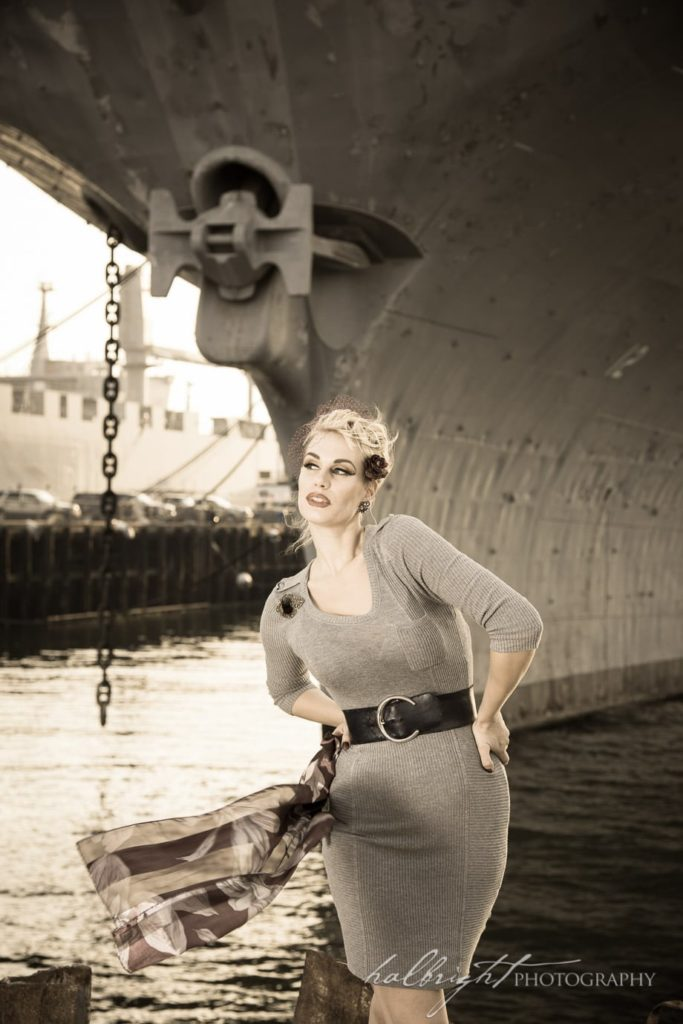 Photo of model in vintage dress posing in front of the U.S.S. Hornet Aircraft Carrier in Alameda, CA
