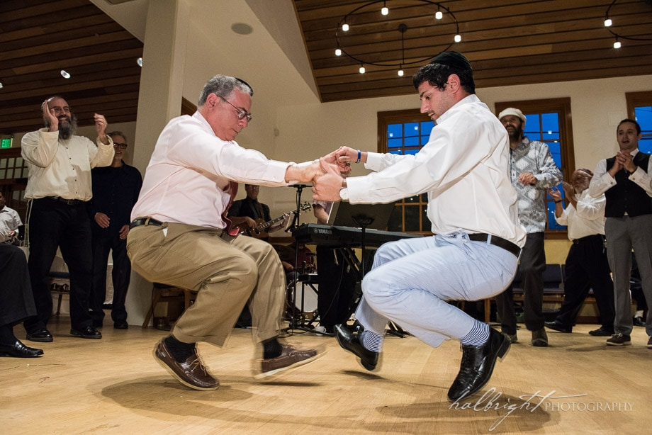 Two guests of the Bridge and Groom dance together in a traditional east european dance while holding hands and crouched above the ground at a traditional jewish wedding in Berkeley, CA at Congregation Beth Israel.