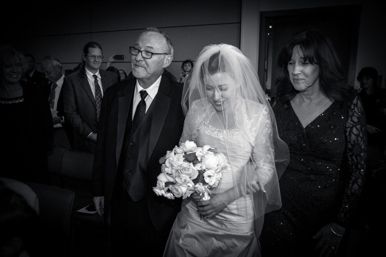 The father of the bride walks his daughter down the while at her wedding