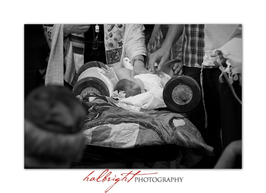 Parents place their hands on their baby during blessing in her naming ceremony at Chochmat Halev, Berkeley, California