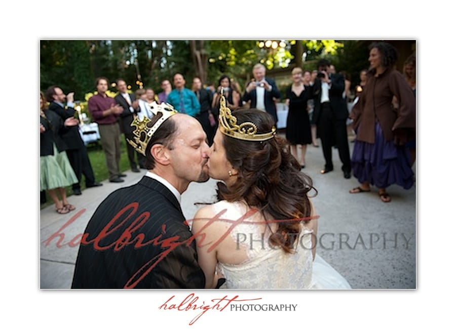 Bride and Groom Kiss while wearing crowns and with their guests looking on - Mills College - Wedding
