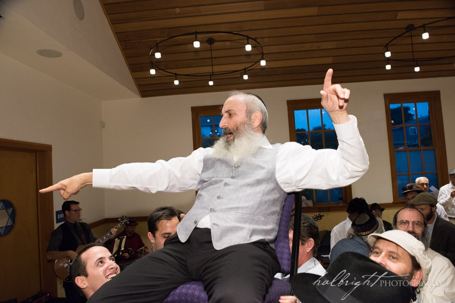 Goom points with enthusiasm as he is raised on a chair at his Berkeley Jewish wedding at Congregation Beth Israel