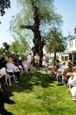 Bride and Groom standing in front of beautiful tree in front of friends and family for their wedding ceremony - Napa Wedding